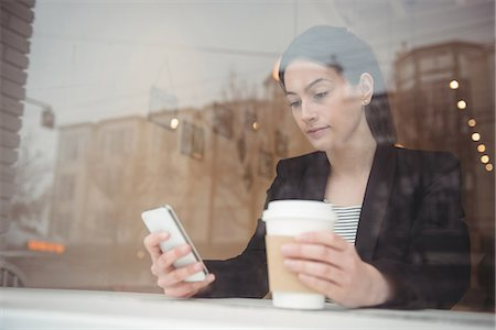 simsearch:6109-08700445,k - Young businesswoman holding disposable coffee cup while using phone in coffee shop Stock Photo - Premium Royalty-Free, Code: 6109-08945417