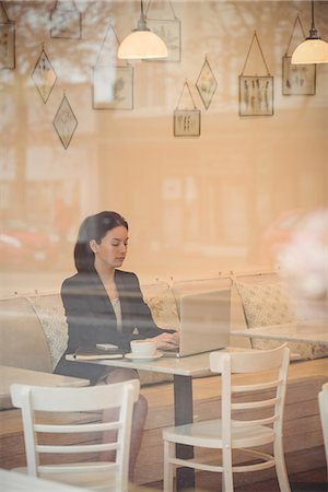 simsearch:6109-08700445,k - Businesswoman using laptop at table in coffee shop Stock Photo - Premium Royalty-Free, Code: 6109-08945414