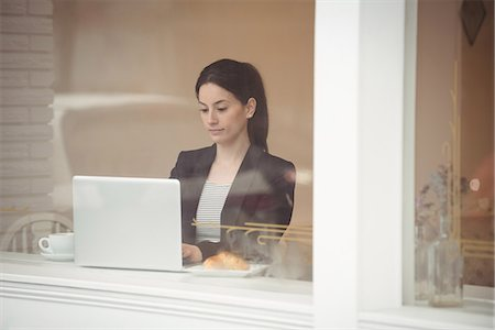 simsearch:6109-08700445,k - Young businesswoman using laptop in coffee shop seen through window Stock Photo - Premium Royalty-Free, Code: 6109-08945415