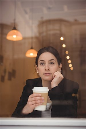 simsearch:6109-08700445,k - Thoughtful young businesswoman holding disposable coffee cup in cafe Stock Photo - Premium Royalty-Free, Code: 6109-08945418