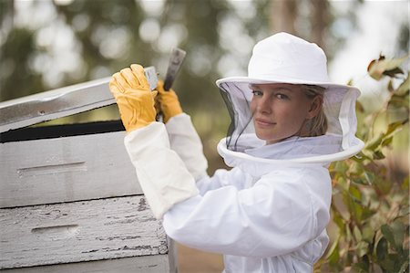 professional (pertains to traditional blue collar careers) - Portrait of female beekeeper opening honeycomb at apiary Stock Photo - Premium Royalty-Free, Code: 6109-08953466