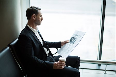 simsearch:6109-08700445,k - Businessman having coffee while reading newspaper in waiting area at airport Stock Photo - Premium Royalty-Free, Code: 6109-08929570