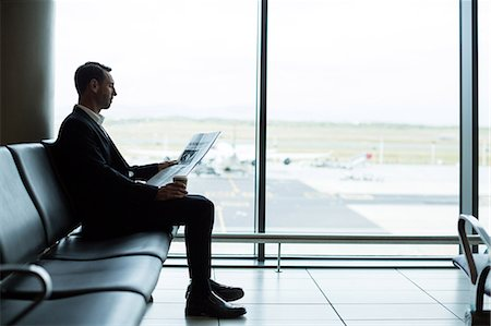 simsearch:6109-08700445,k - Businessman having coffee while reading newspaper in waiting area at airport Stock Photo - Premium Royalty-Free, Code: 6109-08929571