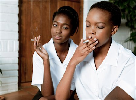 Two African teenage girls sit outside smoking cigarettes Stock Photo - Premium Royalty-Free, Code: 6110-06702679
