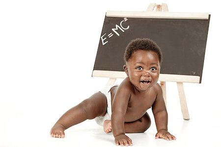 An infant sitting in front of a white background, smiling with a chalkboard in the background Stock Photo - Premium Royalty-Free, Code: 6110-06702749