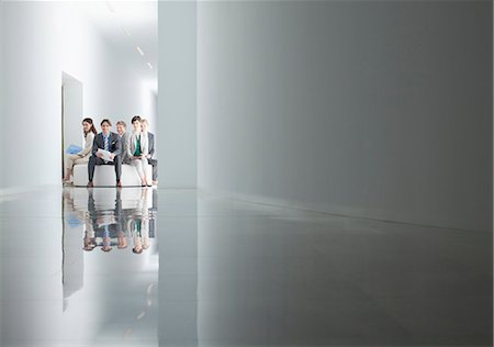 Portrait of business people sitting in circle in corridor Stock Photo - Premium Royalty-Free, Code: 6113-06497788