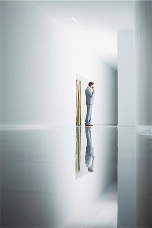 Businessman on cell phone in corridor Stock Photo - Premium Royalty-Free, Code: 6113-06497860