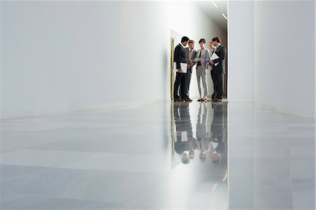 Business people meeting in corridor Stock Photo - Premium Royalty-Free, Code: 6113-06497828