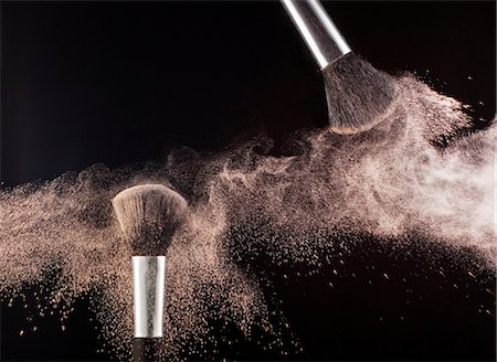 Powder blowing from makeup brushes Stock Photo - Premium Royalty-Free, Code: 6113-06497995