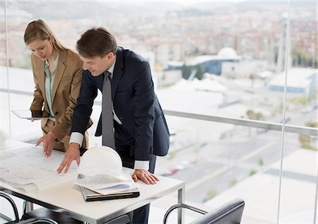 reviewing - Architects reviewing blueprints in office overlooking city Stock Photo - Premium Royalty-Free, Code: 6113-06497927
