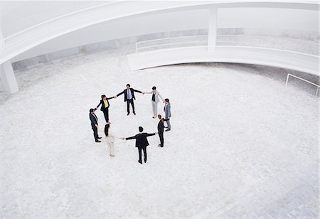 Business people holding hands in circle in courtyard Stock Photo - Premium Royalty-Free, Code: 6113-06497925