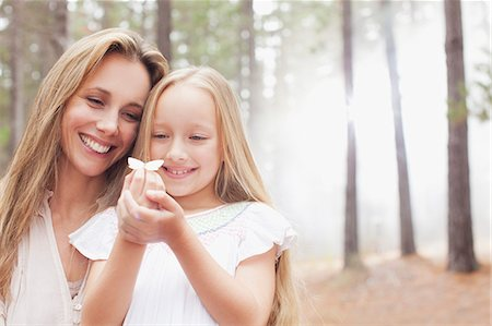 Smiling mother and daughter holding butterfly in woods Stock Photo - Premium Royalty-Free, Code: 6113-06498047