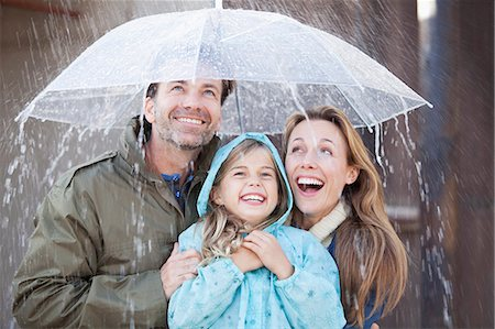people with umbrellas in the rain - Enthusiastic family under umbrella in downpour Stock Photo - Premium Royalty-Free, Code: 6113-06498045