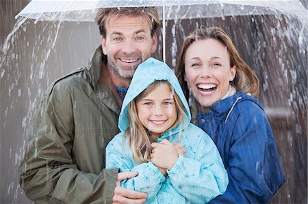 people with umbrellas in the rain - Portrait of enthusiastic family under umbrella in downpour Stock Photo - Premium Royalty-Free, Code: 6113-06498061