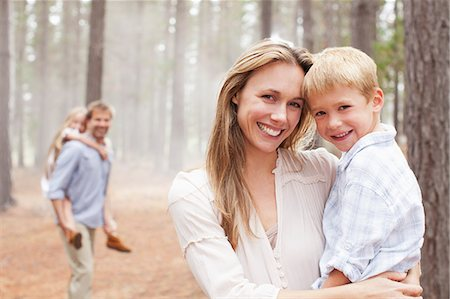 Portrait of smiling mother holding son in woods Stock Photo - Premium Royalty-Free, Code: 6113-06498068