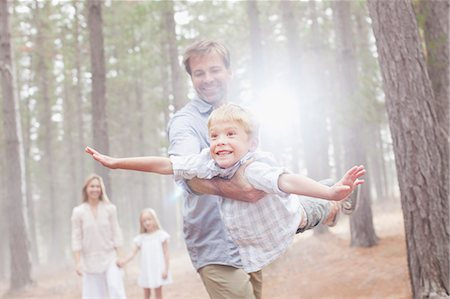 flying happy woman images - Father flying son in sunny woods Stock Photo - Premium Royalty-Free, Code: 6113-06498071