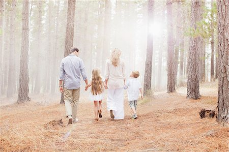 Family holding hands and walking in sunny woods Stock Photo - Premium Royalty-Free, Code: 6113-06498037