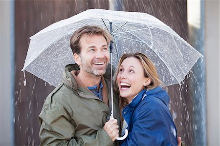 people with umbrellas in the rain - Happy couple under umbrella in downpour Stock Photo - Premium Royalty-Free, Code: 6113-06498039
