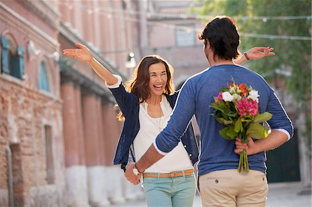 flower greeting - Enthusiastic woman approaching man with flowers behind back Stock Photo - Premium Royalty-Free, Code: 6113-06498162