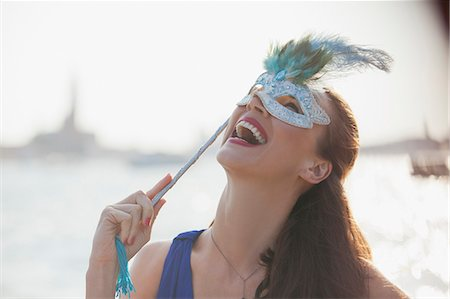Laughing woman with mask at waterfront in Venice Stock Photo - Premium Royalty-Free, Code: 6113-06498123