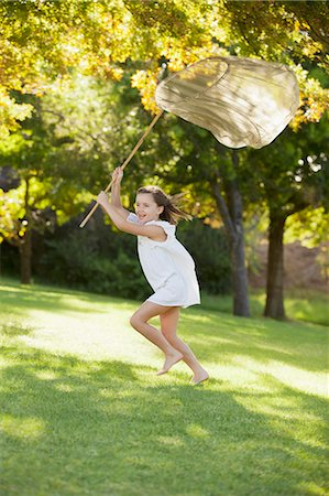 Happy girl running with butterfly net in grass Stock Photo - Premium Royalty-Free, Code: 6113-06498560