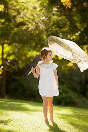 Girl carrying butterfly net in grass Stock Photo - Premium Royalty-Free, Code: 6113-06498571