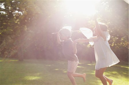 Boy and girl holding hands and running with butterfly nets in grass Stock Photo - Premium Royalty-Free, Code: 6113-06498579