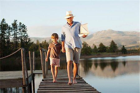 Smiling grandfather and grandson with toy sailboat holding hands and walking along dock over lake Stock Photo - Premium Royalty-Free, Code: 6113-06498584