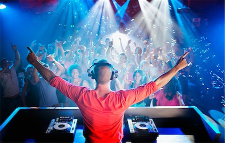 DJ with arms outstretched overlooking dance floor Stock Photo - Premium Royalty-Free, Code: 6113-06498596