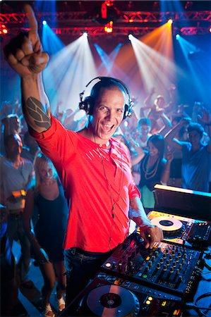 Portrait of enthusiastic DJ at turntable in nightclub Stock Photo - Premium Royalty-Free, Code: 6113-06498641