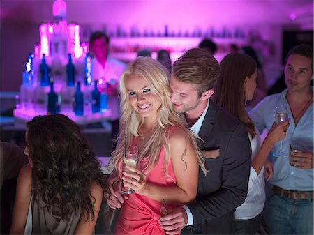 Portrait of smiling couple with cocktails in nightclub Stock Photo - Premium Royalty-Free, Code: 6113-06498645