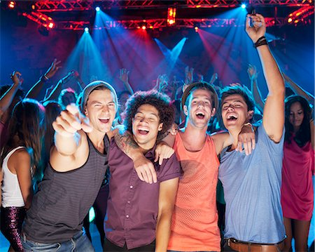Enthusiastic friends cheering on dance floor of nightclub Stock Photo - Premium Royalty-Free, Code: 6113-06498653