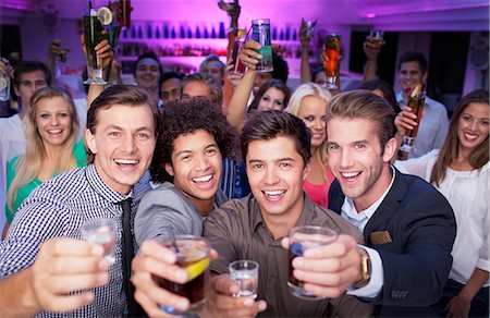 Portrait of enthusiastic crowd drinking cocktails in nightclub Stock Photo - Premium Royalty-Free, Code: 6113-06498663