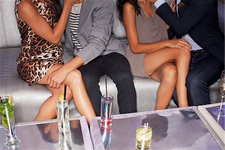 desire - Legs of couples sitting on sofa in nightclub Stock Photo - Premium Royalty-Free, Code: 6113-06498662