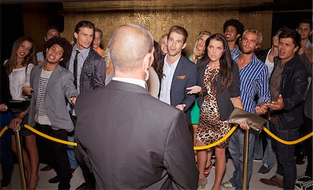 Crowd gesturing to bouncer behind rope outside night club Stock Photo - Premium Royalty-Free, Code: 6113-06498667
