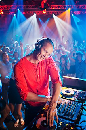 DJ at turntable with crowd on dance floor in background Stock Photo - Premium Royalty-Free, Code: 6113-06498666