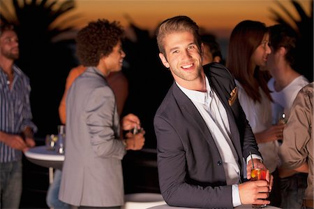 exterior bar - Portrait of smiling man with cocktail on balcony at sunset Stock Photo - Premium Royalty-Free, Code: 6113-06498672