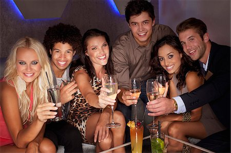 Portrait of smiling friends toasting cocktails in nightclub Stock Photo - Premium Royalty-Free, Code: 6113-06498674