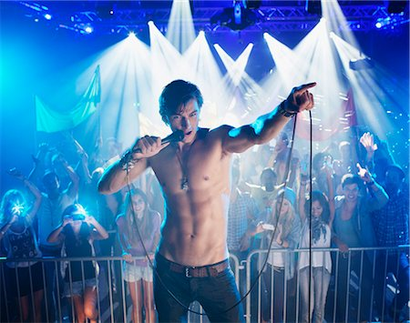 Bare chested singer performing with crowd in background Stock Photo - Premium Royalty-Free, Code: 6113-06498676