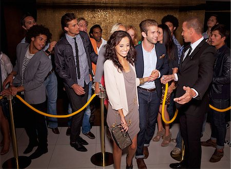 queue club - Bouncer granting couple access outside nightclub Stock Photo - Premium Royalty-Free, Code: 6113-06498681