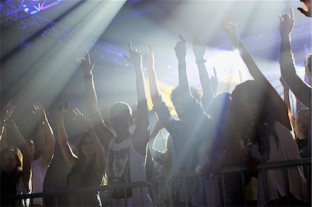 Crowd with arms raised behind railing at concert Stock Photo - Premium Royalty-Free, Code: 6113-06498603