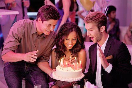 Friends with birthday cake in nightclub Stock Photo - Premium Royalty-Free, Code: 6113-06498605