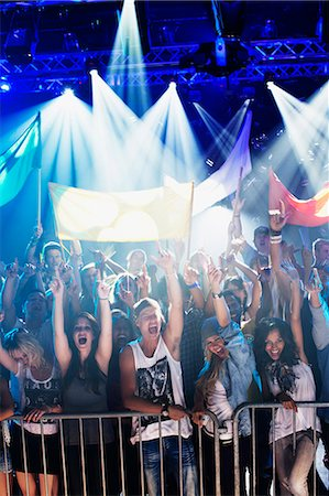 Crowd cheering with arms raised behind railing at concert Stock Photo - Premium Royalty-Free, Code: 6113-06498606