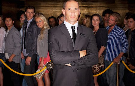 queue club - Portrait of serious bouncer with arms crossed in front of queue at nightclub Stock Photo - Premium Royalty-Free, Code: 6113-06498609