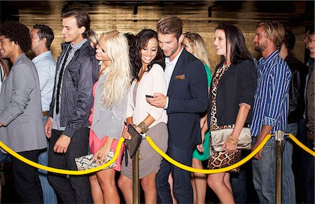 Couple with cell phone standing in queue outside nightclub Stock Photo - Premium Royalty-Free, Code: 6113-06498613