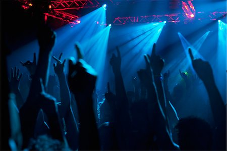 Silhouette of crowd cheering with arms raised at concert Stock Photo - Premium Royalty-Free, Code: 6113-06498617