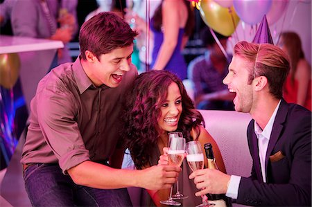 Enthusiastic friends toasting champagne flutes in nightclub Stock Photo - Premium Royalty-Free, Code: 6113-06498616