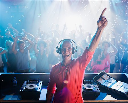 Portrait of enthusiastic DJ with arm raised and people on dance floor in background Stock Photo - Premium Royalty-Free, Code: 6113-06498618