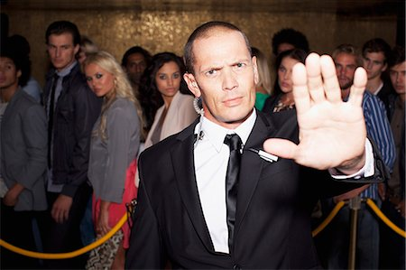 Portrait of bouncer with arm outstretched outside nightclub Stock Photo - Premium Royalty-Free, Code: 6113-06498623