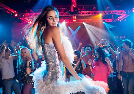 Woman in silver dress with feather boa dancing in nightclub Stock Photo - Premium Royalty-Free, Code: 6113-06498624